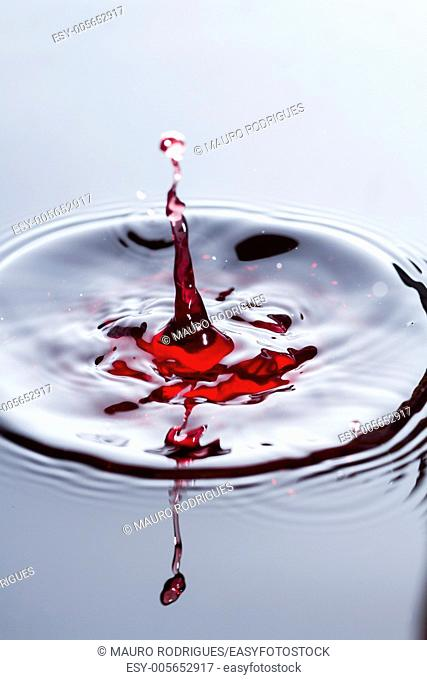 Close view of a droplet of wine hitting a surface of wine