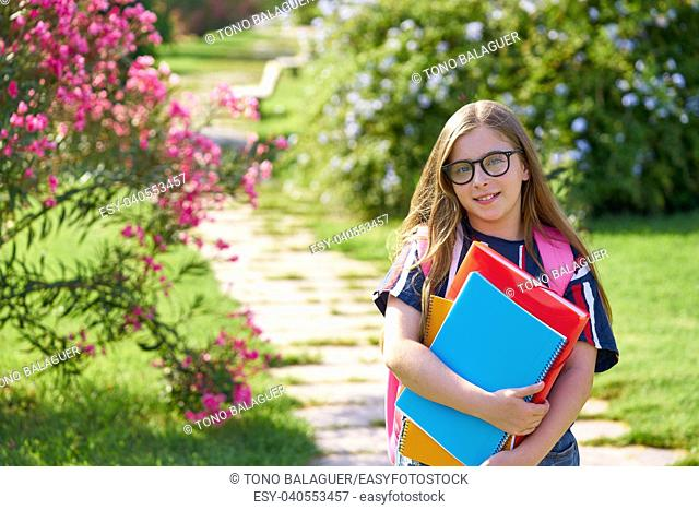 Blond kid student girl with glasses notebook and backpack in the park
