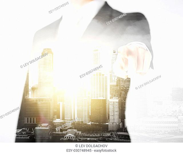 business, choice and people concept - close up of businessman pointing finger at you over city with double exposure