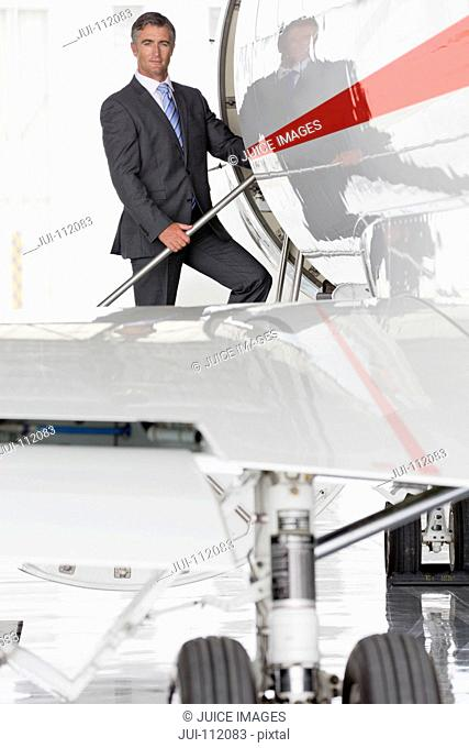 Businessman boarding private jet and looking at camera
