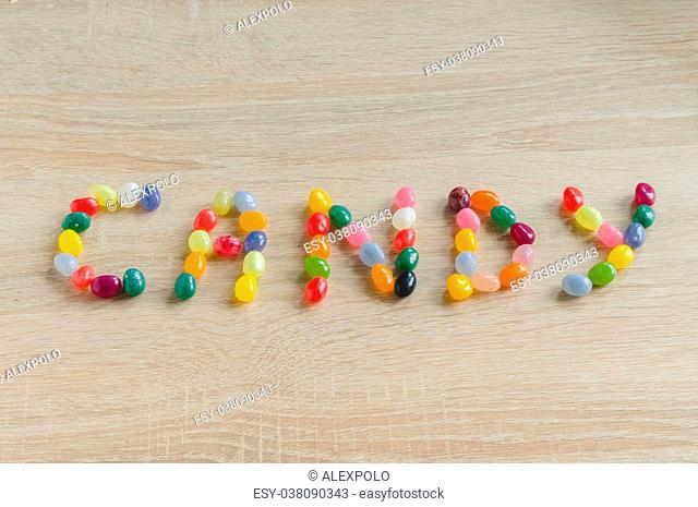 Word candy from jelly beans on wooden background