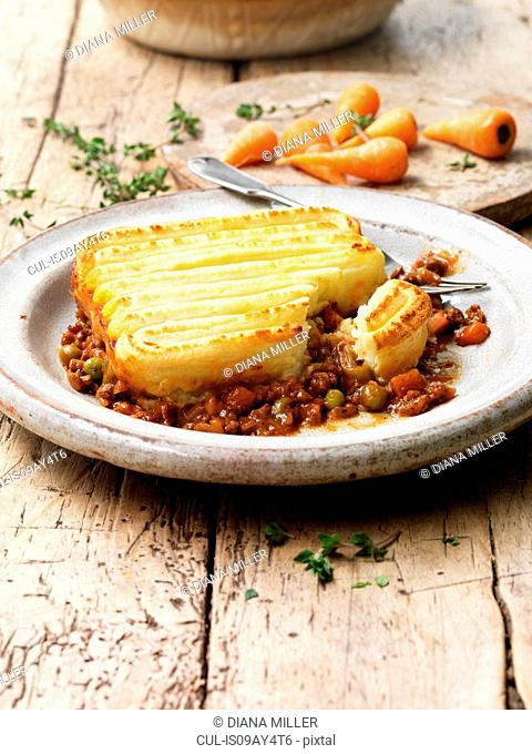 Food, traditional meals, cottage pie on vintage plate, minced beef, peas, carrots, onions, mashed potato, gravy, rustic wooden table