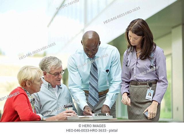 senior couple consulting with doctors at outdoor table