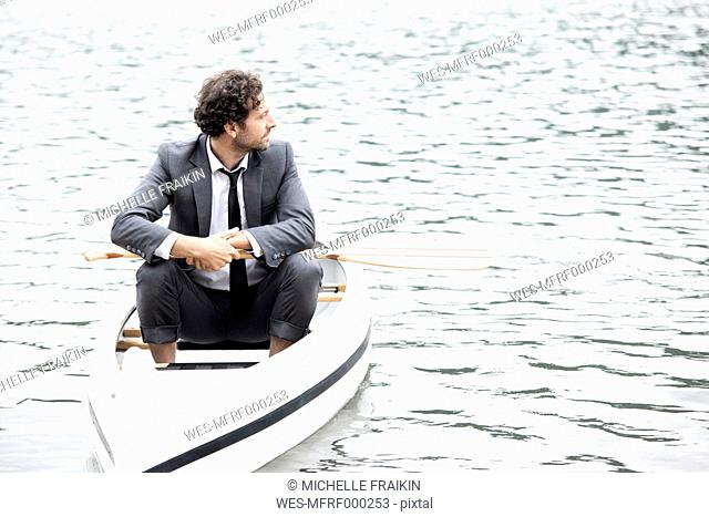 Germany, Rur Reservoir, businessman relaxing in canoe