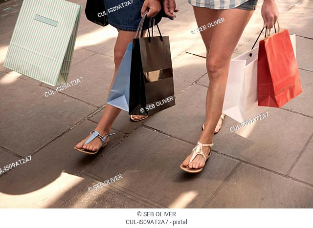 Bare legs and feet of two women carrying shopping bags on city street