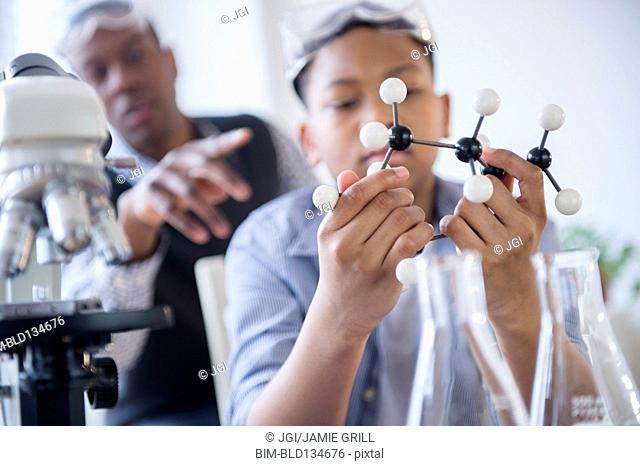 Student examining molecular model in science class