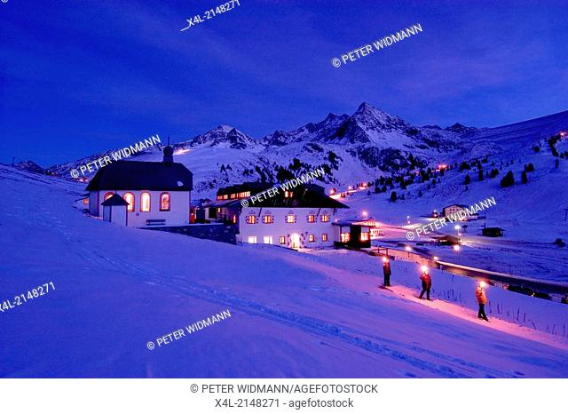 Austria, village in the alps in winter at night, people walk with torches