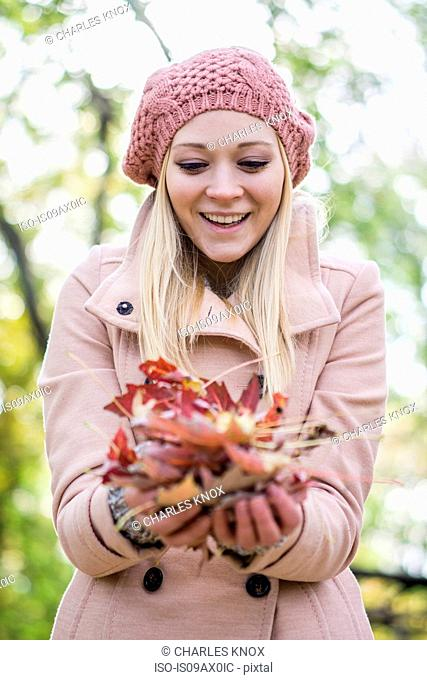 Young woman holding handful of autumn leaves in park