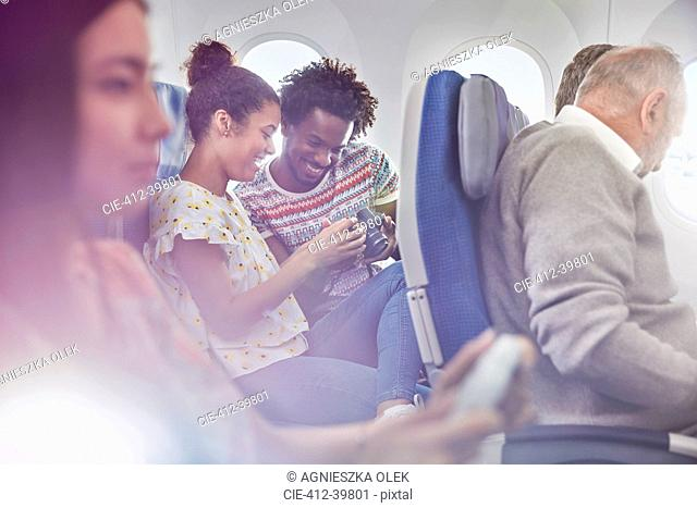 Young couple looking at photos on digital camera on airplane