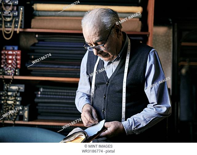 Tailor with measuring tape around his neck inspecting fabric samples