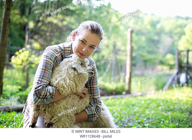 A teenager kneeling and putting her arms around a very curly haired angora goat