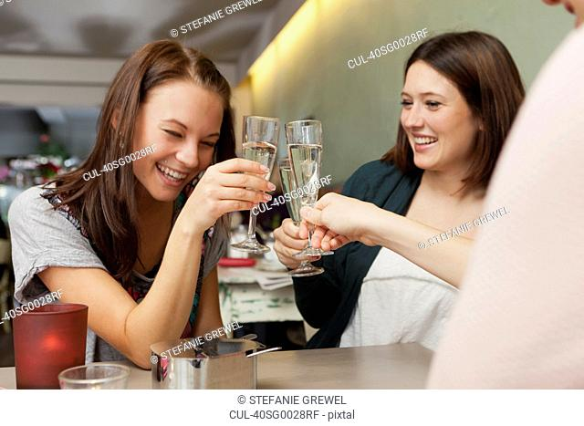 Women toasting with champagne in cafe
