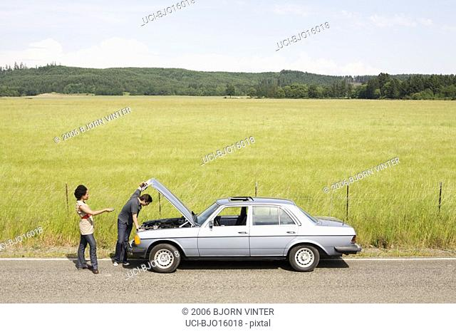Couple looking under car hood