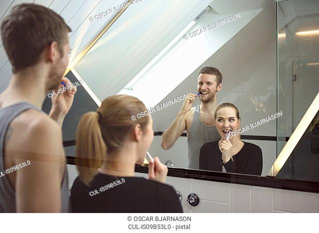 Young couple in bathroom, looking in mirror, brushing teeth