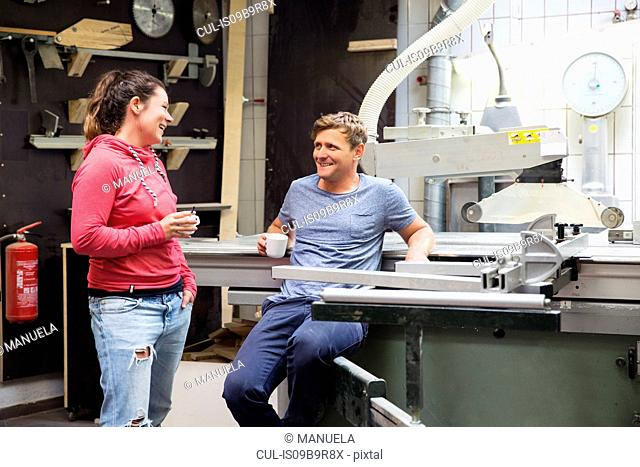 Man and woman in workshop, having conversation