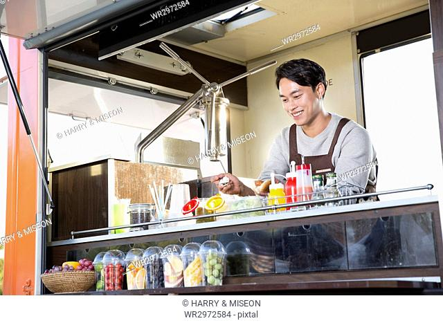 Young smiling vendor at food truck