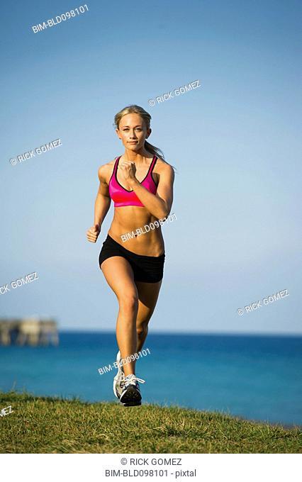 Caucasian woman running near ocean