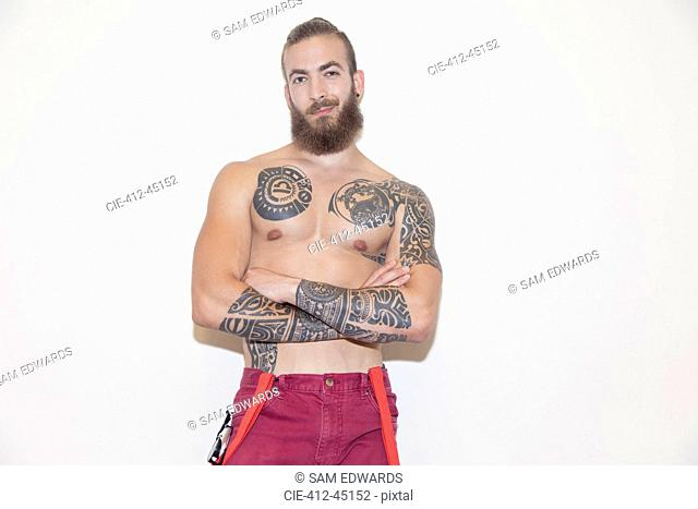 Portrait confident, cool male hipster with bare chest and tattoos