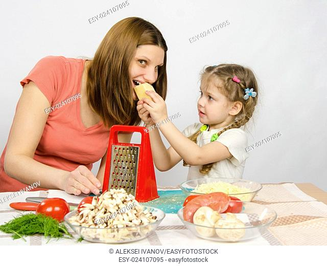 Six-year girl with pigtails giving mom a bite out of a piece of cheese at the kitchen table where they cook together