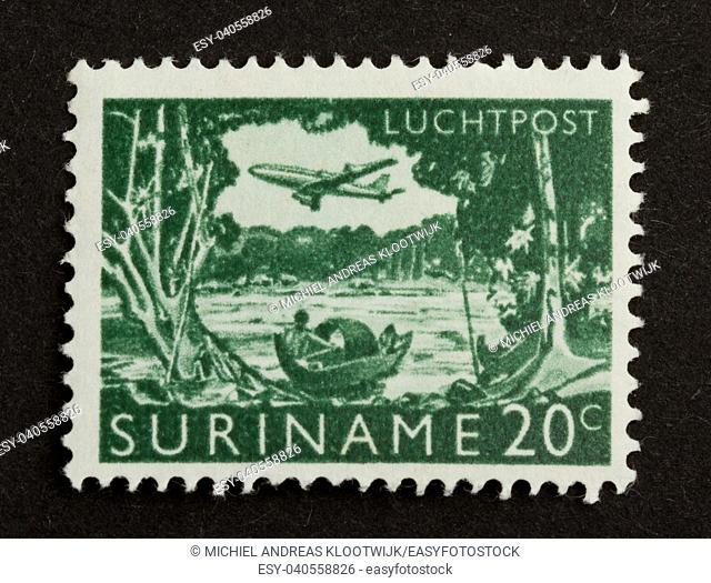 SURINAME - CIRCA 1970: Stamp printed in Suriname shows a river, boat and airplane, circa 1970