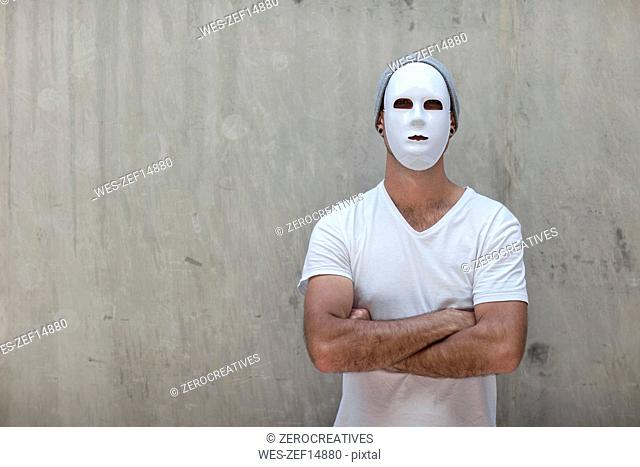 Man wearing a mask standing next to a concrete wall
