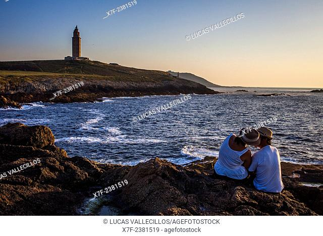 Couple in Punta Herminia gardens,in background Tower of Hercules, Roman lighthouse, Coruña city, Galicia, Spain