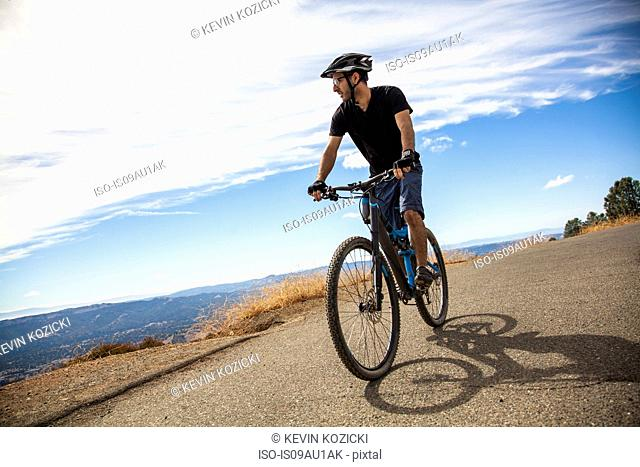 Young male mountain biker looking out at view from rural road, Mount Diablo, Bay Area, California, USA