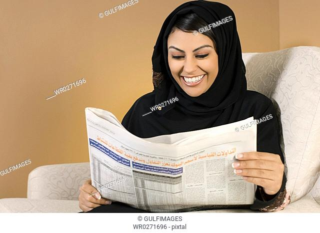 Young woman reading newspaper,smiling