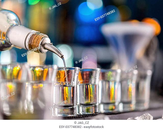 Barman pouring hard spirit into glasses in detail