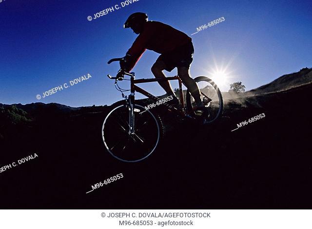 Mountain bike rider coming down hill near sunset Thousand Oaks, CA. USA