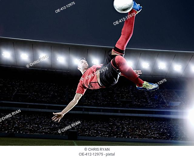 Soccer player kicking ball in mid-air on field