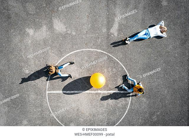 Austria, Aerial, view of basketball field with big ball, mother lying on ground, children sitting
