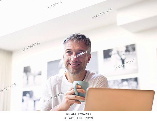 Smiling man drinking coffee at laptop