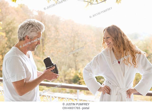 Man with old-fashioned camera photographing woman in bathrobe on autumn balcony