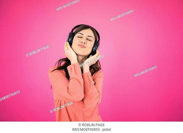 Woman in front of pink wall listening to music on headphones