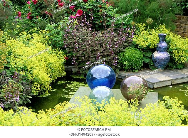 Glass globes and small pond in country garden