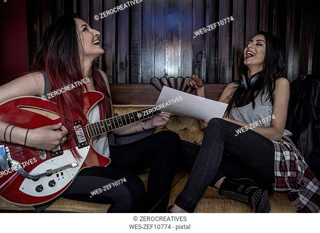 Two happy young women making music together