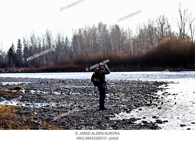 Young man in a camouflage hat wearing a backpack using binoculars at a rivers edge, Florence, Montana