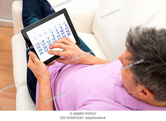 Close-up Of A Man Looking At Calendar In Digital Tablet