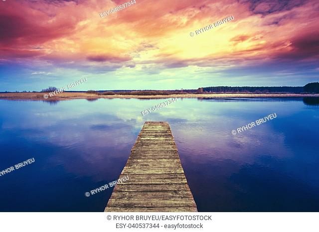 Colorful sunset dramatic sky over wooden boards pier on Calm Water Of Lake, River. Nature Background