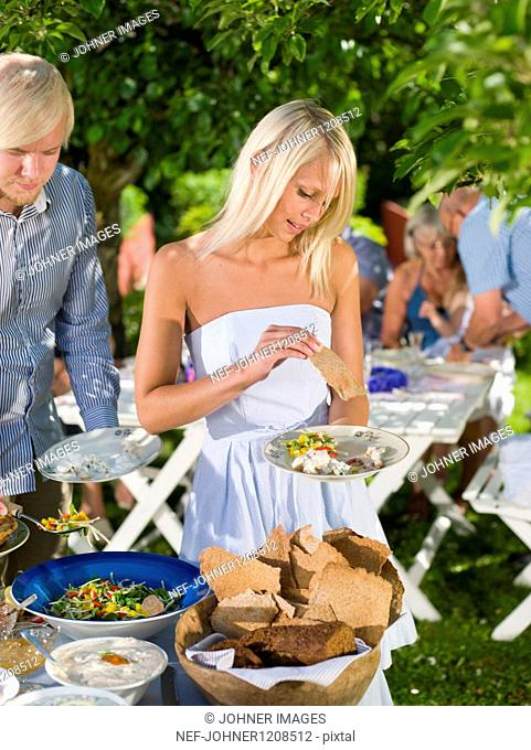 Man and woman having food in garden