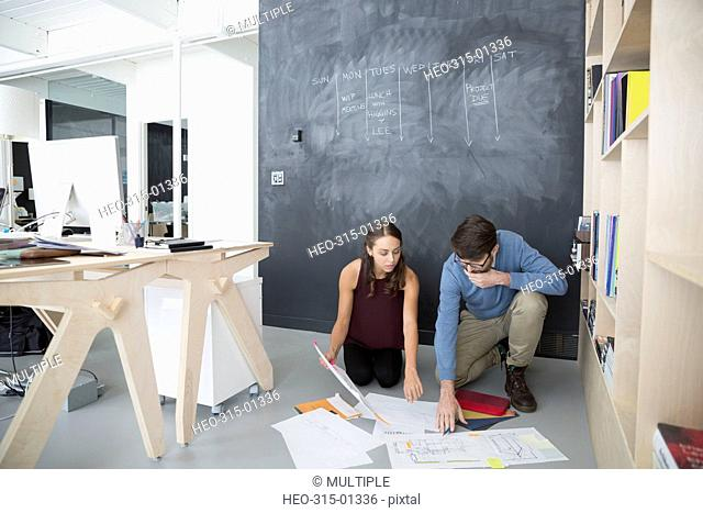 Architects reviewing blueprints on office floor