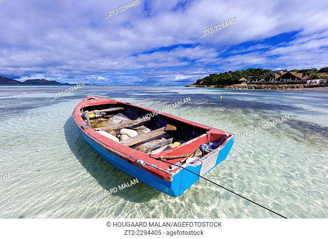 Landscape view of a small fishing boat floating in clear shallow water. La Digue island, Seychelles