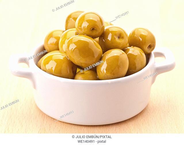 Green olive oiled in white porcelain bowl