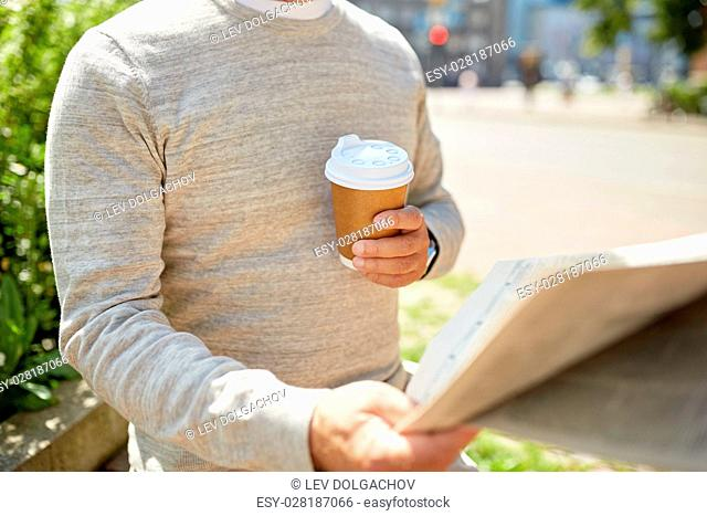old age and people concept - senior man with coffee reading newspaper sitting on street bench