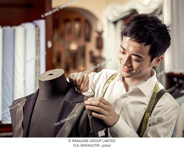 Trainee tailor pinning garment in traditional tailors shop