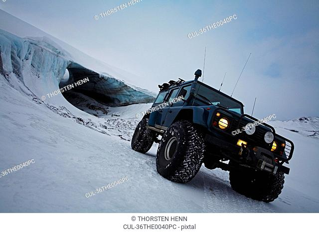 Jeep driving on snow-covered glacier