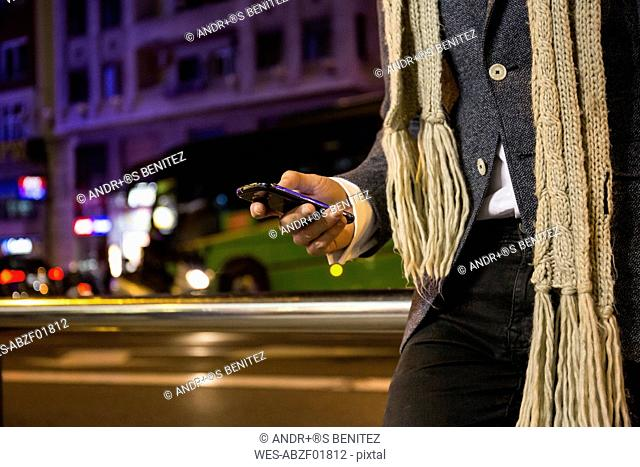 Close-up of man using his cell phone in a street at night