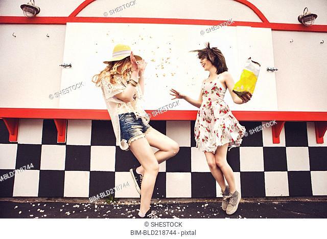 Caucasian friends having popcorn fight outdoors