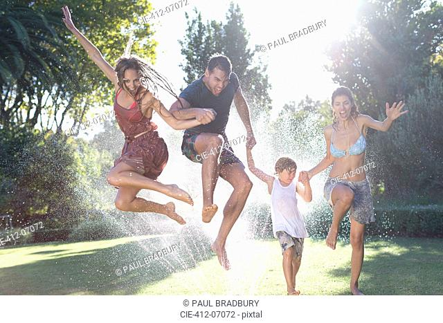 Family jumping in sprinkler